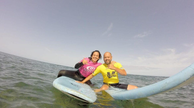 Foto de una hermosa pareja disfrutando en una de nuestras clases de iniciación al surf. K16 SurfSchool Tenerife