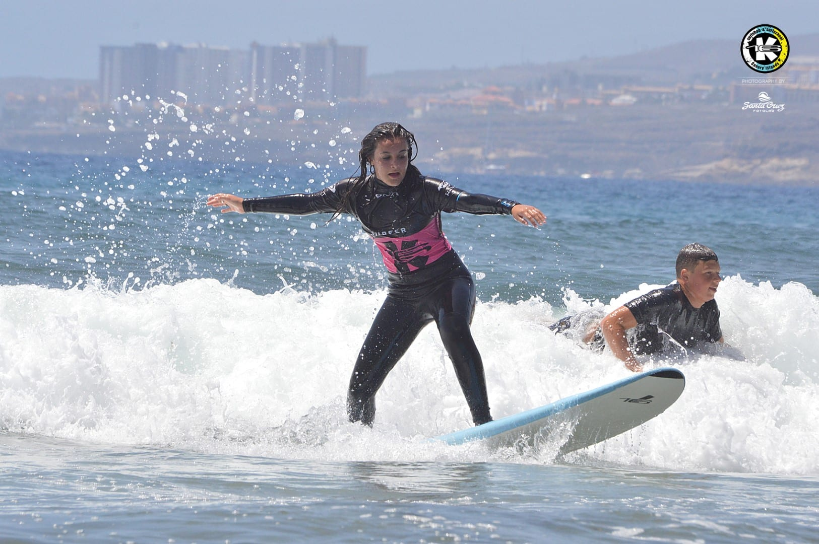 Student surfing a wave during a session of her full 5-day surf course. K16 SurfSchool Tenerife - Las Americas